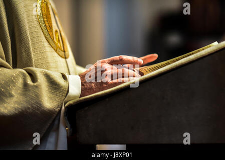 Hands of catholic priest reading a bible. - Stock Photo