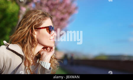 Young redhead woman in sunglasses looking away at spring - Stock Photo