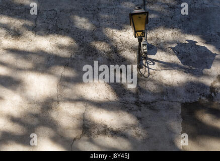 Shadow patterns and a street lamp on a wall on 25th May, 2017, in Lagrasse, Languedoc-Rousillon, south of France. - Stock Photo