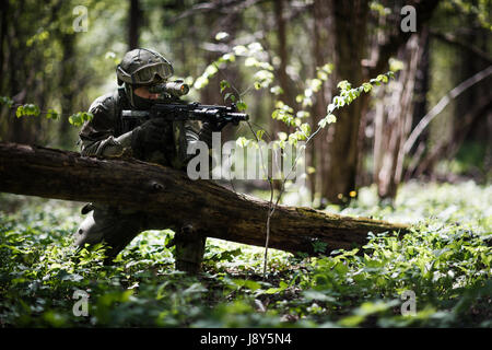 Military man with arms on task in woods during day - Stock Photo