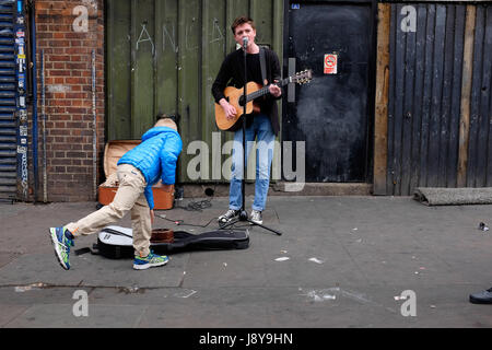 London Street Musician or 'Busker', playing guitar and singing on the streets of Camden Town, London. - Stock Photo