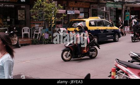 lady with two children on a Motor Bike in Traffic at Soi Buakhao and Soi Diana Pattaya Thailand's Most Dangerous - Stock Photo