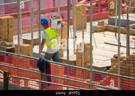 A building site worker or hod carrier or labourer carrying some cement in a bucket - Stock Photo