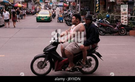 Fat Man Driving a Motor Bike in Traffic at Soi Buakhao and Soi Diana Pattaya Thailand's Most Dangerous Intersection - Stock Photo