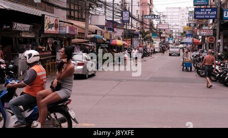 Girl on the back of Motor Bike in Traffic at Soi Buakhao and Soi Diana Pattaya Thailand's Most Dangerous Intersection - Stock Photo