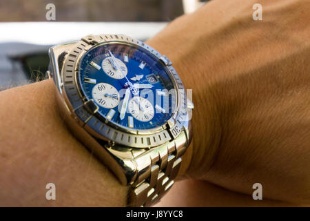 Luxury Breitling Chronomat Evolution watch with blue face on man's wrist  Model Release: Yes.  Property release: - Stock Photo