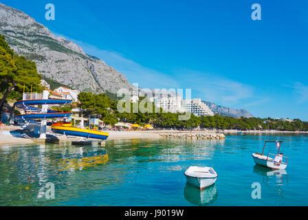 Plaza Donja Luka, the main beach, with boats and water slide, Makarska, Dalmatia, Croatia - Stock Photo