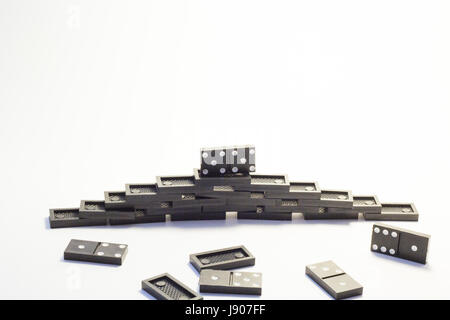 Knuckles of black dominoes are combined in a pyramid on a white background - Stock Photo