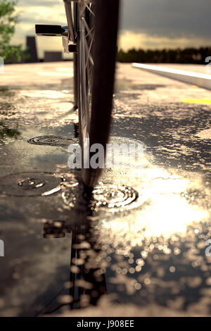 3d rendering of bicycle tire standing on puddle in front of blurred asphalt and evening sunshine - Stock Photo