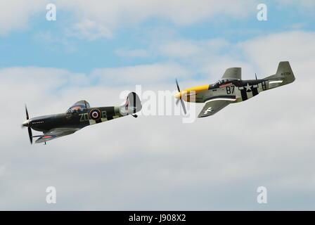 Spitfire fighter MH434 and P-51D Mustang Ferocious Frankie perform at the Dunsfold airshow in Surrey, England on - Stock Photo
