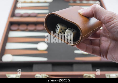 Readying to roll backgammon dice on the brown and cream backgammon board blurred in the background. Focusing on - Stock Photo