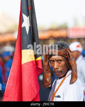 Dili, East Timor. Man in traditional dress holding flag of East Timor - Stock Photo