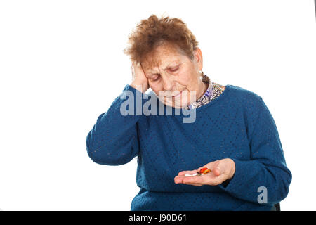 Picture of a senior woman having a headache, holding her pills - Stock Photo