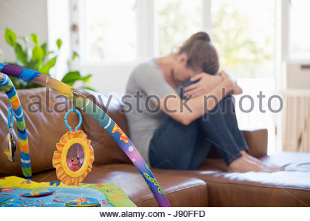 Unhappy Mother Suffering With Post Natal Depression Sits On Sofa - Stock Photo