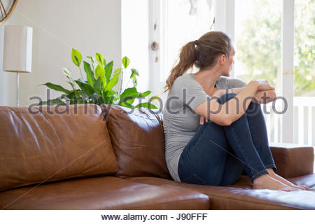 Depressed Woman Sitting On Sofa And Looking Out Of Window - Stock Photo