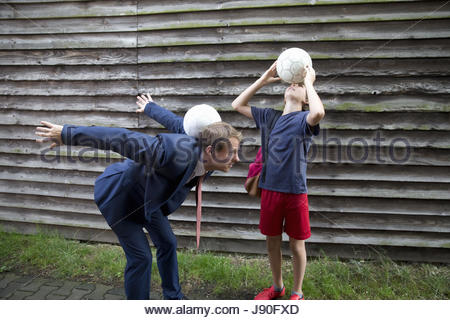 Businessman Father Playing Soccer With Teenage Son - Stock Photo