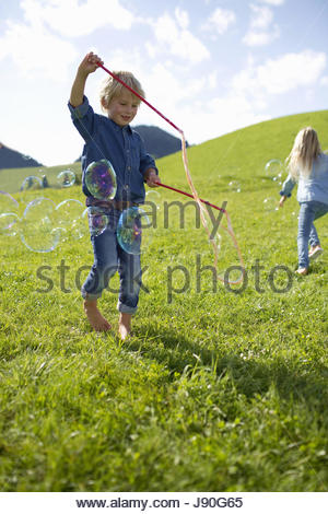 Children Making Giant Bubbles In Countryside - Stock Photo