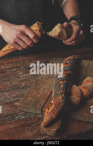 Male hands break the baguette - Stock Photo