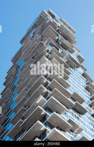 View straight up from the opposite streetcorner showing the irregular pattern of projecting concrete balconies. - Stock Photo