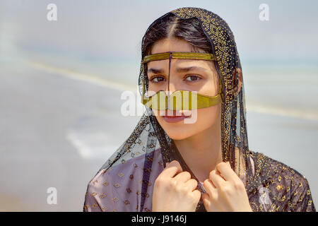 Close-up portrait of an Iranian girl in traditional Islamic dress of southern Iran. - Stock Photo