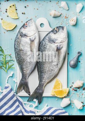 Fresh Sea bream or dorado raw uncooked fish with seasoning - Stock Photo