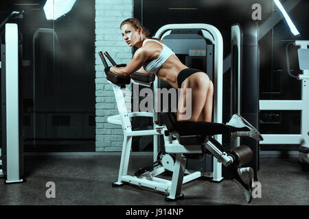 Woman on the machine for bodybuilders doing exercise. She shakes her legs. - Stock Photo