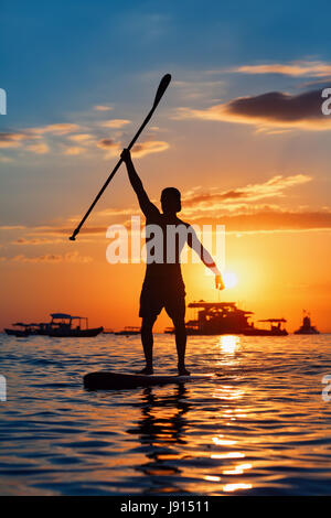 Paddle boarder. Black sunset silhouette of young sportsman paddling on stand up paddleboard. Healthy lifestyle. - Stock Photo