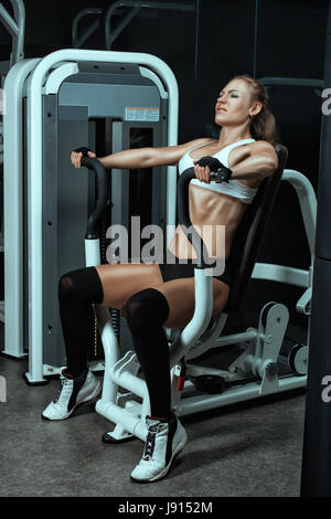 Girl shakes her arm muscles on the machine for bodybuilders. She in the fitness gym. - Stock Photo