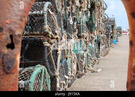 Crab / Lobster pots stacked on the quayside Bridlington harbour, framed through a rusty railing. Photograph was - Stock Photo