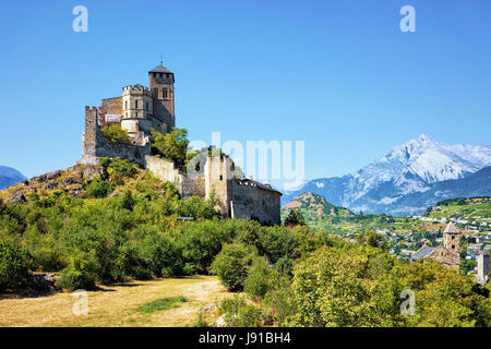 Ancient Valere Basilica on the hill at Sion, Canton Valais, Switzerland. Bernese Alps on the background - Stock Photo