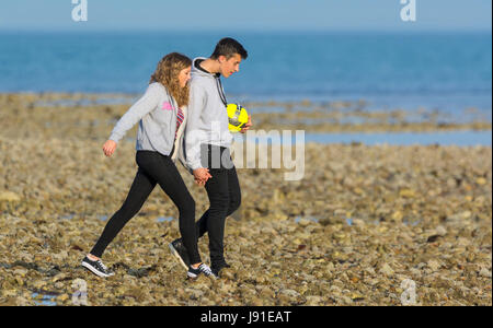 Young couple taking an evening walk along the beach hand in hand. - Stock Photo