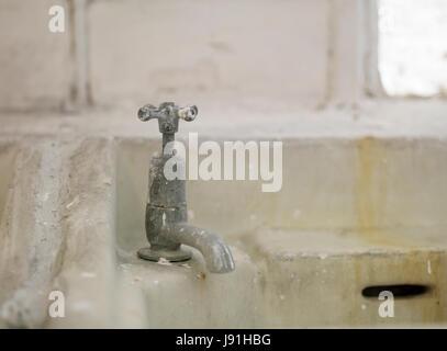 dirty white bathroom sinks in toilet block - Stock Photo