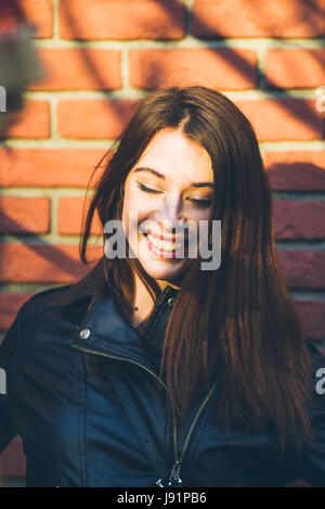 Young beautiful brunette portrait, warm sunset light and shadow pattern created by tree branch - Stock Photo