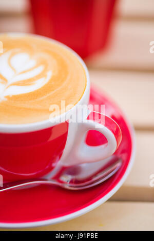 Close-up of cup of Cappuccino coffee with some cool design on the foam - Stock Photo