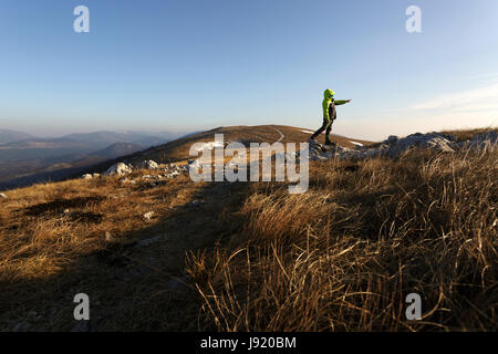 Young boy atanding on the top of the mountain covered with tall grass, Golic, Slovenia. - Stock Photo