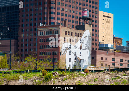 View Chicago River Illinois Downtown riverside buildings old high-rise low-rise large graffiti seated figure water - Stock Photo