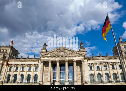 the reichstag in berlin with germany flags - Stock Photo