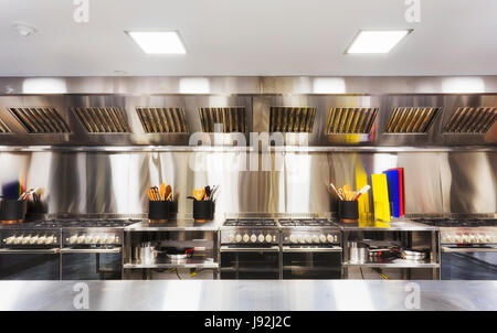 Modern clean equipped kitchen with stainless steel cook tops, cooking tables, utensils and small appliances. - Stock Photo