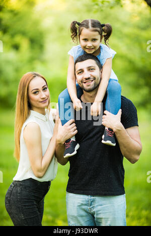 Young family of three having fun together outdoor. Pretty little daughter on her father back. Father carrying daughter - Stock Photo