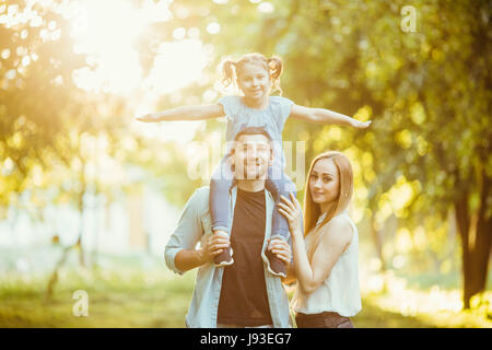 family Mom and Dad holding daughter on his back and have fun in the park. - Stock Photo