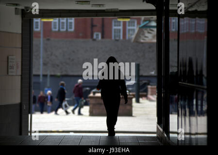 cityscape silhouette of woman leaving entrance to Argyle street train station - Stock Photo