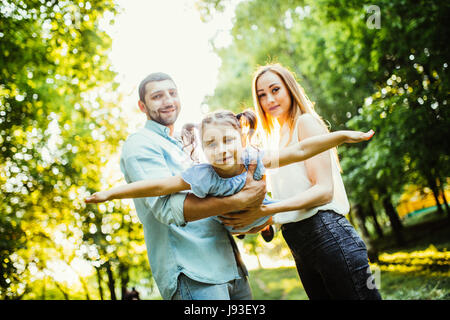 Happy family with one child having fun together in summer city park - Stock Photo