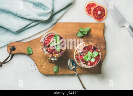 Healthy breakfast. Greek yogurt, granola, blood orange layered parfait in glasses with mint leaves on wooden board - Stock Photo