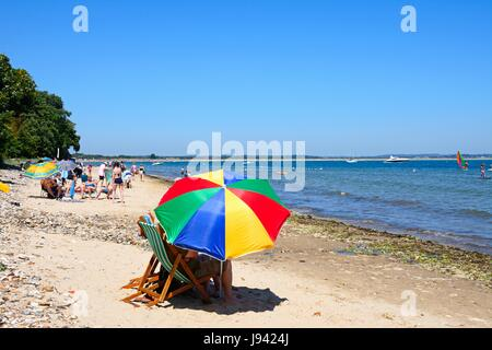 Holidaymakers relaxing on the beach with a colourful parasol in the foreground, Studland Bay, Dorset, England, UK, - Stock Photo
