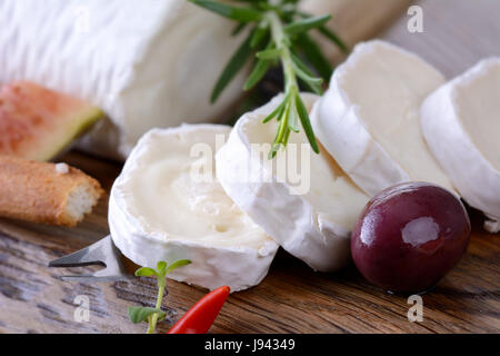 Goat cheese with figs and black olives on a wooden cutting board - Stock Photo