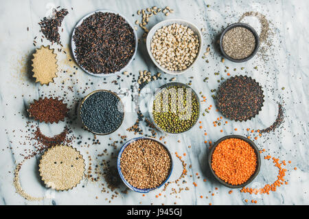 Variety of raw grains, beans, cereals over marble background - Stock Photo
