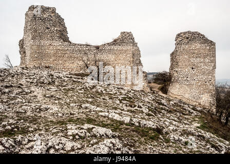 ruins of Sirotci hradek castle on rocky hill withDevin hill on the background in spring Palava mountains in South - Stock Photo
