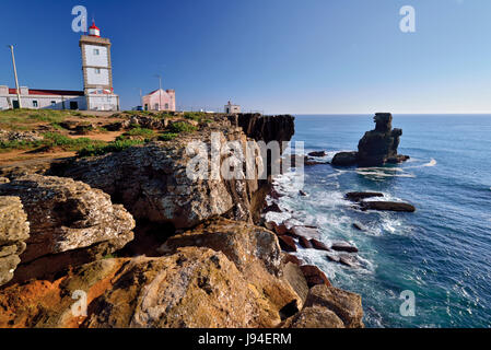 Lighthouse and rocky cliffs at Cape Carvoeiro in Peniche - Stock Photo