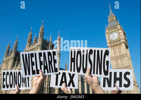 Hands holding election signs protesting modern British social issues of economy, tax, welfare, housing, health at - Stock Photo