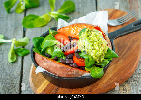 Baked whole sweet potato with guacamole and black beans in a cast-iron frying pan. Love for a healthy vegan food - Stock Photo